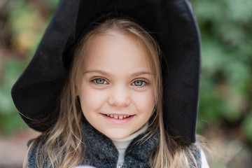 little girl in whitch costume celebrate Halloween outdoor and have a fun.