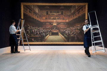 Sotheby's staff remove ladders after posing for a photograph with Banksy's 'Devolved Parliament' which has an estimated value of 1.5-2 million British pounds ahead of forthcoming sale in London