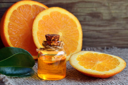 Orange essential oil in a glass bottle and fresh fruits on old wooden table.Citrus oil for skin care, spa, wellness, massage, aromatherapy and natural medicine.Selective focus.