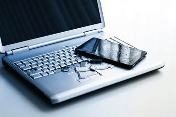 A silver laptop with a broken keyboard and a tablet with a cracked display. A close-up picture of part of broken laptop and cracked screen on a tablet.