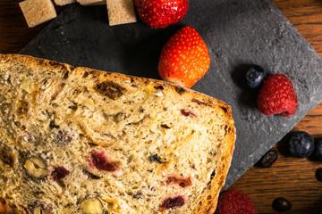 Détail sur une tranche de pain aux fruits secs et raisin sec, abricot sec, noisette, noix, cranberry, à la croûte dorée sur un plat en ardoise avec des fruits frais fraises et cassis et du sucre roux