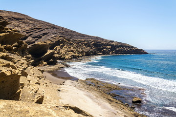 Small amazing beach hidden between dramatic cliffs on Tenerife, Canary Islands, Spain, sunny summer day