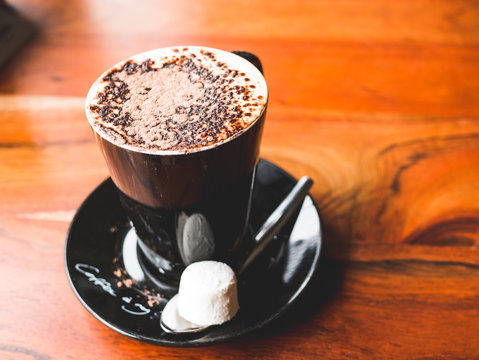 Cup of hot chocolate with dark brown chocolate foam on top with sugar