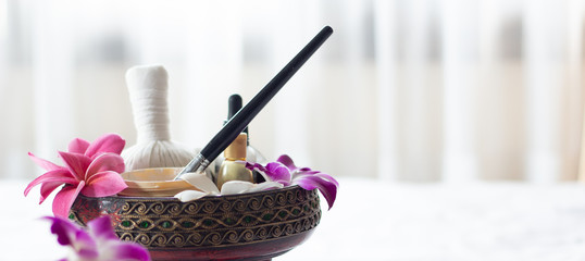 Spa Thai massage accessories in luxury salon on white towel in vase. Oil and beauty care equipment for relaxation and treatment indoors.