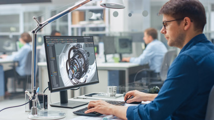 Over the Shoulder Shot of Engineer Working with CAD Software on Desktop Computer, Screen Shows Technical Details and Drawings. In the Background Engineering Facility Specialising on Industrial Design