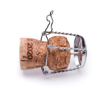 A champagne or sparkling wine cork from 2020 lying on the ground. Isolated on white background.