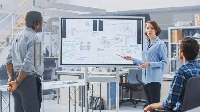In Industrial Design Facility Team of Engineers and Technicians have a Meeting, Female Specialist Leads Briefing, Talks and Draws on Digital Interactive Whiteboard with Car Prototype Concepts