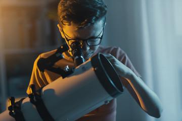 Obraz Smart boy using a telescope and watching stars - fototapety do salonu
