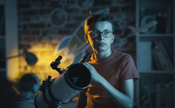 Smart boy using a telescope and watching stars