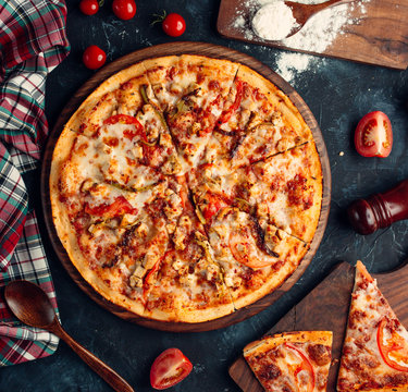 Chicken pizza with tomato, bell peppers, mushroom, and cheese