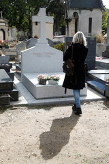 A woman takes a picture of the grave where late French President Jacques Chirac will be buried at Montparnasse cemetery in Paris