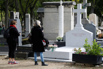 Women take pictures of the grave where late French President Jacques Chirac will be buried at Montparnasse cemetery in Paris