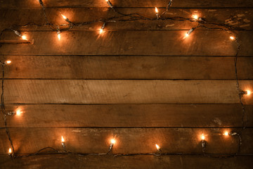 Christmas lights bulb decoration on old wood plank, frame border design. Merry Christmas and New Year holiday background. vintage color tone. Wall mural