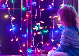 Happy little cute, beautiful girl 5 years old is sitting on the window and playing with Christmas lights and  Christmas decoration. Dark-blue theme.