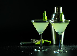Light green daiquiri alcoholic cocktail in conical cocktail glasses, decorated with lime slices, a shaker, a strainer and half a lime on a dark background with water drops
