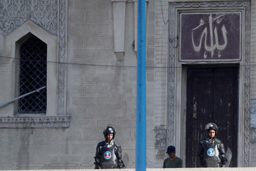 Riot police officers watch from the doorway of Sidi Bishr mosque after Friday prayers in Alexandria