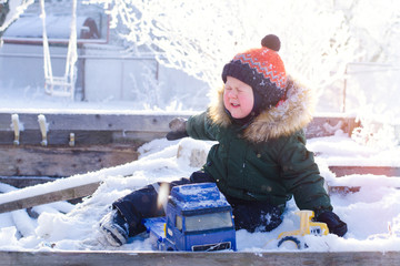 A boy in a bright orange hat plays with toys in a snowy winter Park