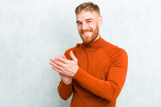young red head man wearing turtle neck feeling happy and successful, smiling and clapping hands, saying congratulations with an applause against concrete wall