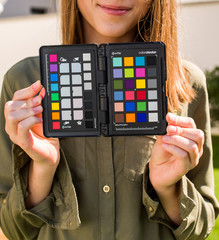 PARIS, FRANCE - SEP 30, 2018: Professional model holding Color Passport by X-Rite Color Reference Targets and camera calibration sfotware before the professional photo session shooting