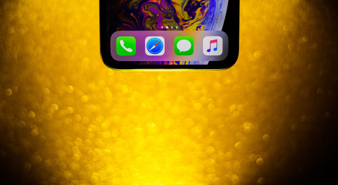 PARIS, FRANCE - OCT 2, 2018: iPhone Xs Max home screen button macro shot with glitter sparkle background gold colored Message, Safari, Telephone and Apple music icons app