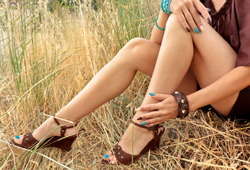 Beautiful long legs with a pedicure and multi-colored oval manicure on a girl in a summer field.
