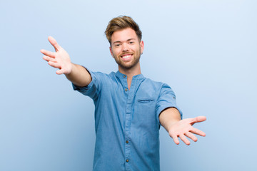 young businessman smiling cheerfully giving a warm, friendly, loving welcome hug, feeling happy and adorable against blue background