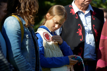 Climate change teen activist Greta Thunberg looks at the tassel from a gift given by Assembly of First Nations National Chief Perry Bellegarde before joining a climate strike march in Montreal