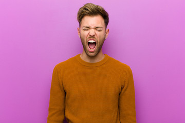 young man shouting aggressively, looking very angry, frustrated, outraged or annoyed, screaming no against purple background