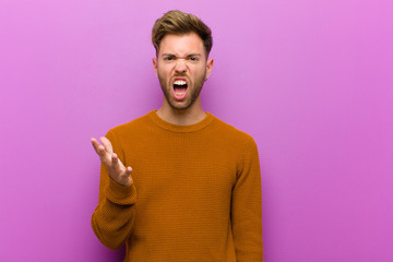 young man looking angry, annoyed and frustrated screaming wtf or what's wrong with you against purple background