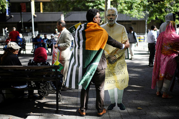 A man wearing a flag of Azad Kashmir holds a cardboard cutout of the Prime Minister of India Modi during a protest in solidarity with the people of Kashmir