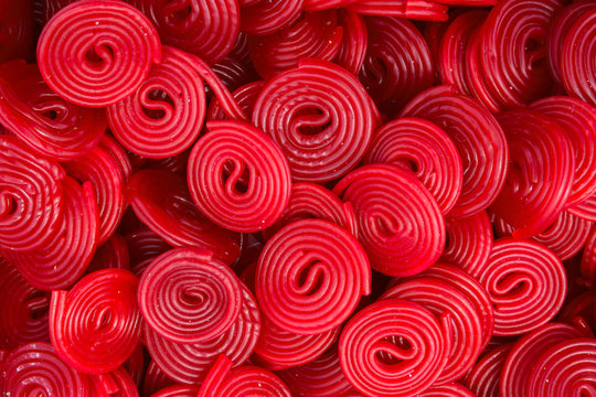 Heap of red strawberry licorice wheels swirl shape candies at supermarket. Creative sweet food confectionery pattern. Kids treats birthday party sugar addiction unhealthy diet concept