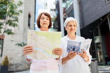 tourism, travel and friendship concept - happy senior women with city guide and map on tallinn street
