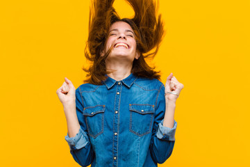 young pretty woman looking extremely happy and surprised, celebrating success, shouting and jumping against yellow background
