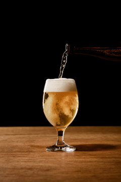 beer pouring from bottle in glass isolated on black