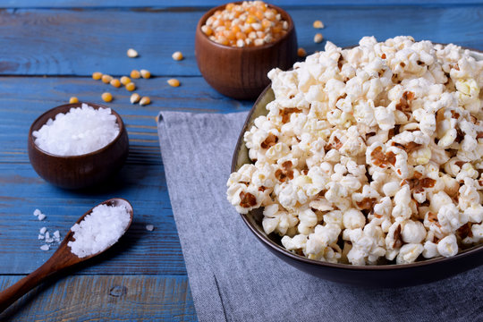 Popcorn, unpopped kernels and sea salt on blue wooden table
