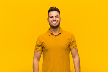 young hispanic man looking happy and goofy with a broad, fun, loony smile and eyes wide open against orange wall