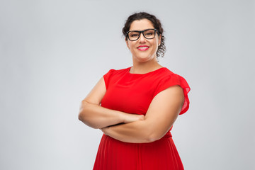 vision, education and eyesight concept - happy woman in red dress and glasses with crossed arms over grey background