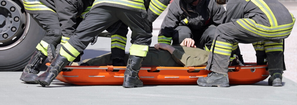 firefighters put a wounded person on a stretcher