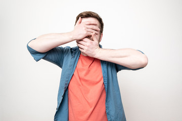 Man in a red t-shirt and blue shirt covers his face with his hands and spread his elbows in different directions, on a white background.