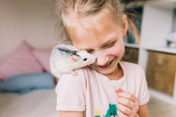 Laughing little girl holding a pet rat in her hands