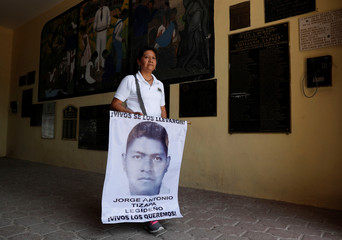 Hilda Legideno Vargas, mother of one of missing students of the Ayotzinapa Teacher Training College holds a banner with an image of her son before a march in Iguala in the state of Guerrero, in Tixtla