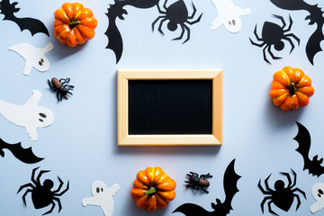 Happy halloween holiday concept. Halloween decorations, picture frame, spiders, bats, ghosts, pumpkins on blue background. Flat lay, top view, overhead.