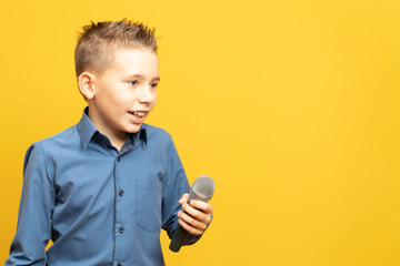 Child with a microphone, in a shirt, on a yellow background