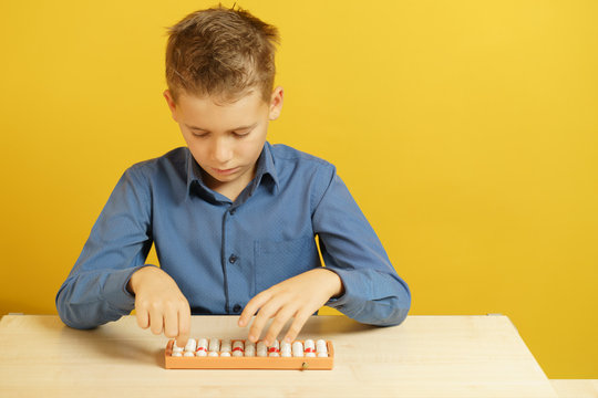 A boy in blue shirt sits at the table and decides task on mental arithmetic