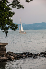 Sailboat with white sails on the lake