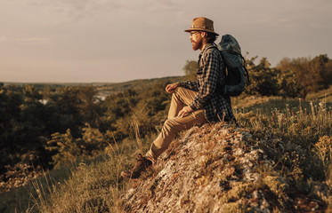 Calm man in hat with backpack sitting on hill and looking along