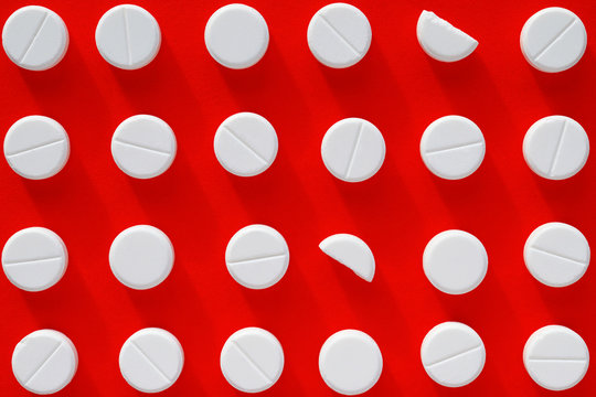 White pills on red background. One pill is broken in two. Top view. Flat lay
