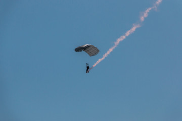 German skydiver in the air with a tail of smoke