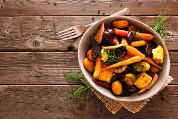 Acrylic Prints Brussels Bowl of roasted autumn vegetables, top view over a rustic wood background