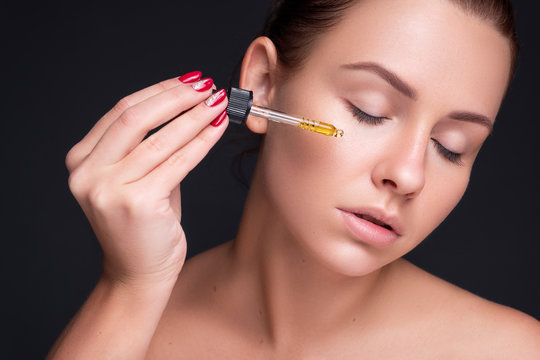 Brunette caucasian woman apply hyaluronic acid from a bottle using a pipette. Flawless clean skin. Beauty skin care concept